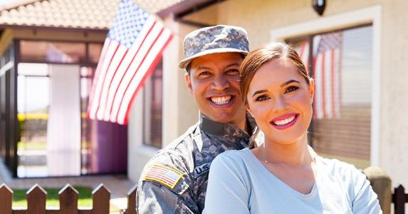 military man and wife standing outside house 573x300 - About